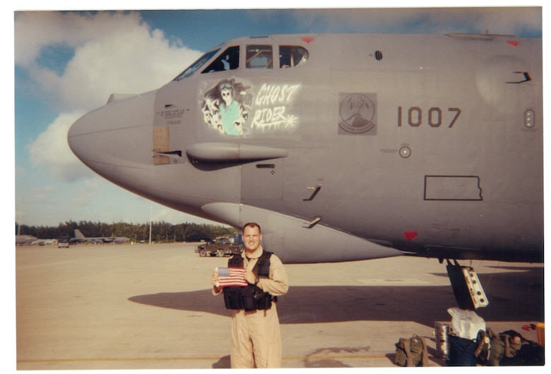 Capt. Doug Warnock, 20th Expeditionary Bomb Squadron, holds an American flag in front of The B-52H Stratofortress 61-007, aka Ghost Rider, at Diego Garcia, July 2002. Warnock now serves as the 5th Bomb Wing operations group commander. (Courtesy Photo)