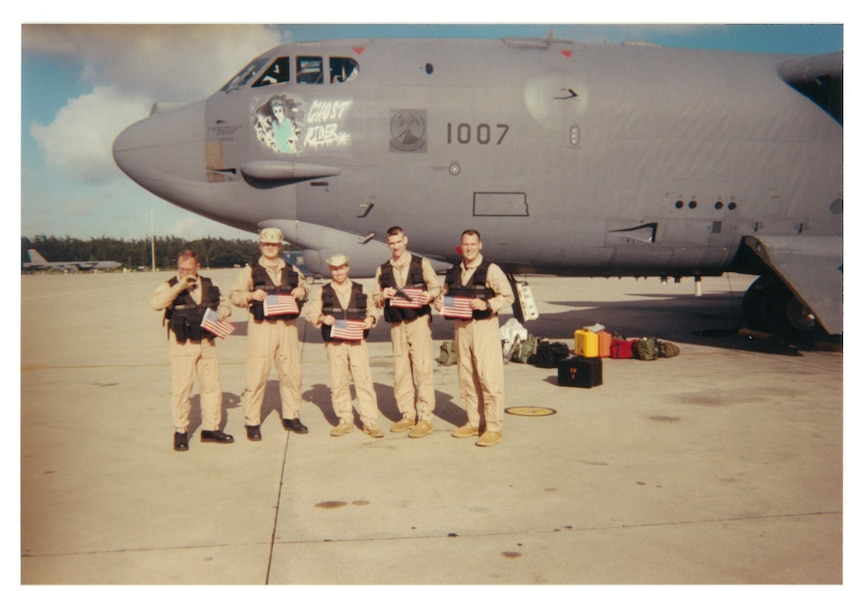 Capt. Doug Warnock (right) and other members of the 20th Expeditionary Bomb Squadron hold American flags in front of The B-52H Stratofortress 61-007, aka Ghost Rider, at Diego Garcia, July 2002. Warnock now serves as the 5th Bomb Wing operations group commander. (Courtesy Photo)