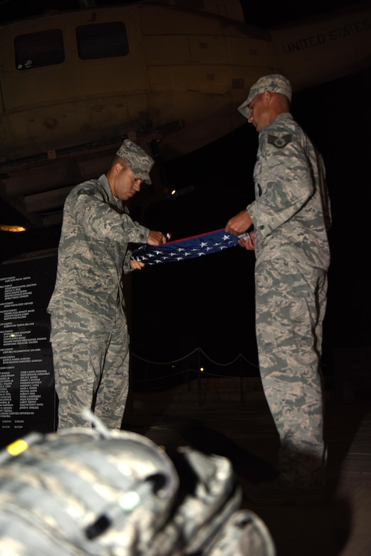 U.S. Air Force Staff Sgt. Tyler Wiseman, 17th Security Forces Squadron Military Working Dog kennel master, and Staff Sgt. Mark Riley, 17th SFS unit trainer, fold the American flag during the Jacobson Memorial Ruck March at the Mathis Field Vietnam Memorial, San Angelo, Texas, Sept. 28, 2016. Members from Goodfellow Air Force Base rucked 12-miles in honor of Airman 1st Class Elizabeth Jacobson's death in Operation Iraqi Freedom in 2005. (U.S. Air Force photo by Airman 1st Class Caelynn Ferguson/Released)