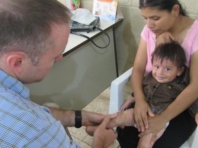 U.S. Army Maj. Jonathan Reagan, Joint Task Force Bravo Medical Element physical therapist, is applying a low load, static stretch technique to an eight-month-old burn victim during a weekly visit to Centro de Rehabilitación Integral de Comayagua, August 3, 2016, where he treats Honduran patients and provides follow-up care for their rehabilitation process. JTF-Bravo regularly partners with the partner nation Ministries of Health to provide various levels and types of medical care in a variety of locations throughout Central America, to include physical therapy, trauma, preventive medicine and dental. (U.S. Army photo by 1st Lt Jenniffer Rodriguez)