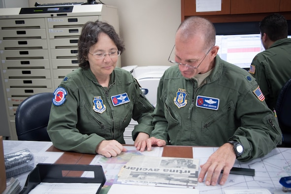 """Lt. Col. Troy """"Bear"""" Anderson, 53rd Weather Reconnaissance Squadron pilot and Lt. Col. Valerie Hendry 53rd WRS aerial reconnaissance weather officer, look at an old newspaper clipping before the final flight of their Air Force careers. (U.S. Air Force photo/Senior Airman Heather Heiney)"""