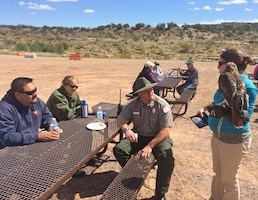 ABIQUIU LAKE, N.M., -- A representative from The Wildlife Center shows park manager John Mueller (center) and other volunteers an interpretive red tailed hawk, Sept. 24, 2016.