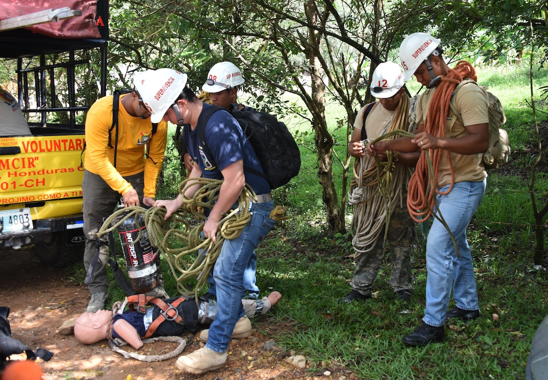 """Honduran PUMCIR (Personal Utilizado en Misiones Contra Incendio y Rescate – Personnel Used in Fire and Rescue) volunteers prepare the ropes, SCUBA tanks and """"Bartholomew"""" the 50-pound dummy they would use to conduct cave extraction search and rescue training in the Comayagua National Park near El Volcan, Honduras, Sept. 24, 2016. A number of the PUMCIR members on this particular exercise were part of the PUMCIR ELITE-RESCUE team. (U.S. Air Force photo by Capt. David Liapis)"""