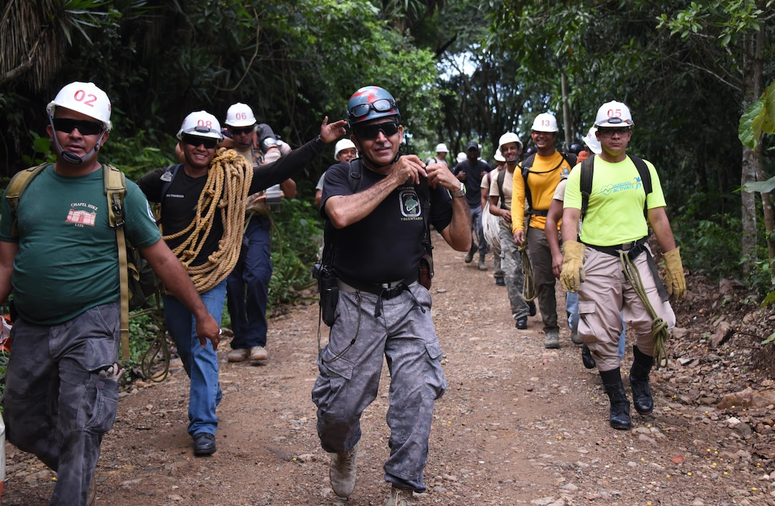 Herberth Gaekel (middle), 612th Air Base Squadron Fire Department liaison at Soto Cano Air Base, Honduras, and PUMCIR (Personal Utilizado en Misiones Contra Incendio y Rescate – Personnel Used in Fire and Rescue) founder and instructor, leads 13 Honduran and seven U.S. volunteers on the first leg of a six-mile round-trip hike into the mountains of Comayagua National Park near El Volcan, Honduras, Sept. 24, 2016, to conduct realistic search and rescue training. The all-volunteer group was comprised of Honduran Bomberos and a doctor from the surrounding region and seven U.S. Air Force Airmen assigned to Joint Task Force-Bravo that included firefighters and Personnel Recovery Coordination Cell members. (U.S. Air Force photo by Capt. David Liapis)
