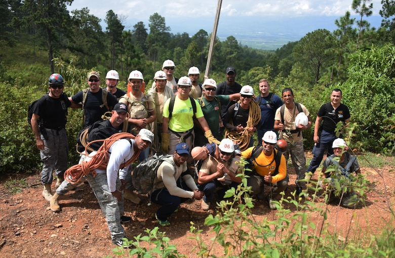 Thirteen Honduran PUMCIR (Personal Utilizado en Misiones Contra Incendio y Rescate – Personnel Used in Fire and Rescue) volunteers and six U.S. Air Force Airmen assigned to Joint Task Force-Bravo who included firefighters and Personnel Recovery Coordination Cell members, led by Herberth Gaekel (left), 612th Air Base Squadron Fire Department liaison at Soto Cano Air Base, Honduras, and PUMCIR founder and instructor, pose for a photo midway through a three-mile hike up to a cave located in Comayagua National Park near El Volcan, Honduras, Sept. 24, 2016, to conduct search and rescue training. Gaekel seeks to involve U.S. service members in order to provide them an opportunity to share with and learn from their Honduran counterparts as well as to encourage positive relationship building between the two nations. Gaekel said the training he provides significantly augments what training the volunteers, who are also often full or part-time Bomberos, already receive, and in many cases would not receive if not for his program. (U.S. Air Force photo by Capt. David Liapis)