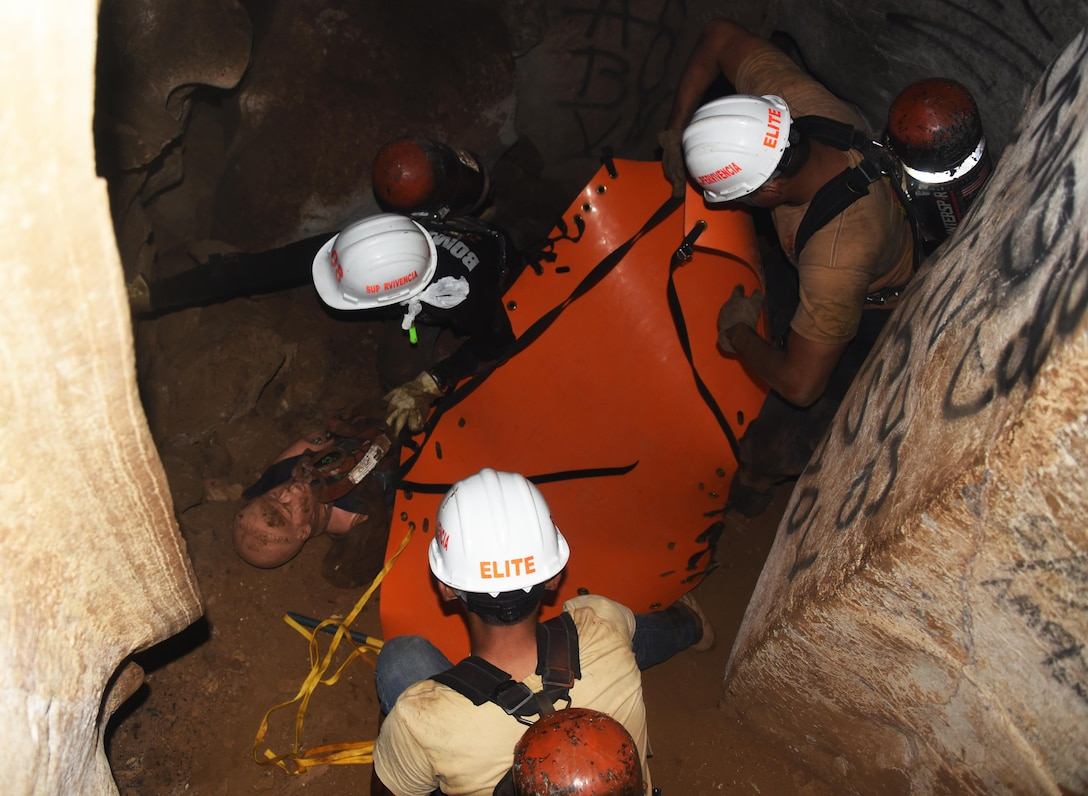"""Honduran PUMCIR (Personal Utilizado en Misiones Contra Incendio y Rescate – Personnel Used in Fire and Rescue) volunteers prepare to remove """"Bartholomew,"""" a 50-pound training dummy on a roll-up stretcher from inside a cave in the Comayagua National Park near El Volcan, Honduras, Sept. 24, 2016 during search and rescue training. Three groups of trainees were given five minutes from the time they entered the cave to safely extract the """"victim"""" from more than 150 feet inside the mountain. (U.S. Air Force photo by Capt. David Liapis)"""