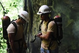 Honduran PUMCIR (Personal Utilizado en Misiones Contra Incendio y Rescate – Personnel Used in Fire and Rescue) volunteers prepare to leave their search and rescue training site at a large cave in Comayagua National Park near El Volcan, Honduras, Sept. 24, 2016. The training involved extracting a 50-pound dummy from the cave on a roll-up stretcher in under five minutes while wearing SCUBA tanks and other necessary safety gear in order to simulate a real-world scenario. (U.S. Air Force photo by Capt. David Liapis)