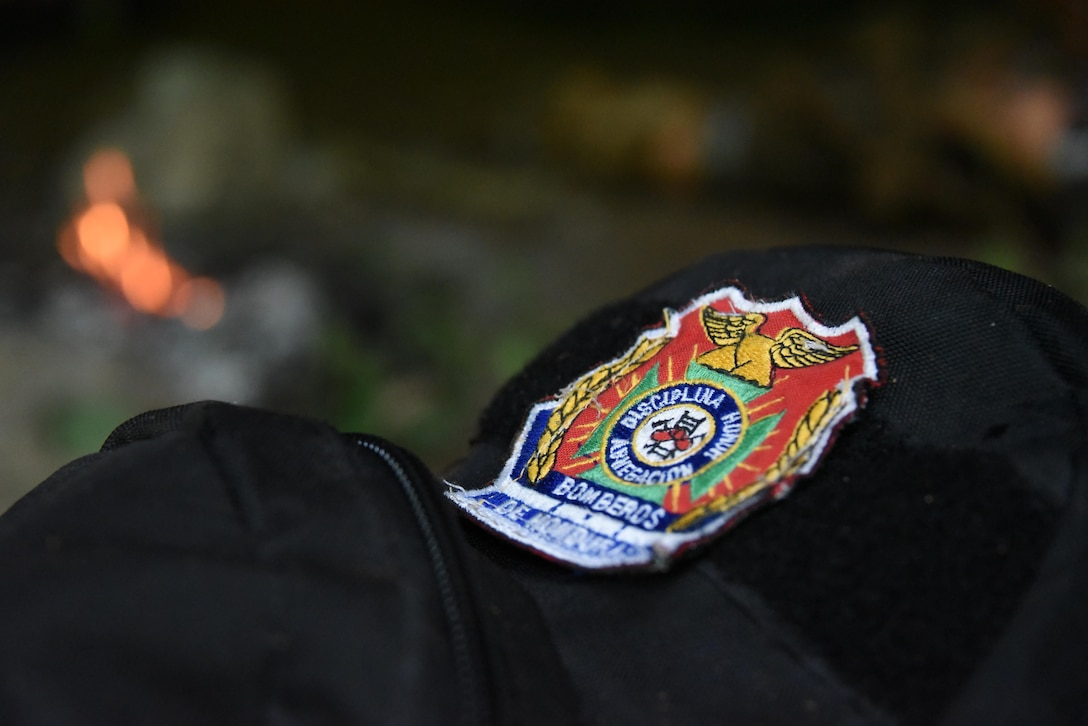 """A backpack belonging to a Honduran PUMCIR (Personal Utilizado en Misiones Contra Incendio y Rescate – Personnel Used in Fire and Rescue) volunteer, bearing the Honduran Fire Department """"Bomberos"""" patch, sits outside a cave in Comayagua National Park near El Volcan, Honduras, Sept. 24, 2016. Herberth Gaekel, 612th Air Base Squadron Fire Department liaison at Soto Cano Air Base and PUMCIR founder and instructor said the training he provides significantly augments what training the volunteers, who are also often full or part-time Bomberos, already receive, and in many cases would not receive if not for his program. (U.S. Air Force photo by Capt. David Liapis)"""