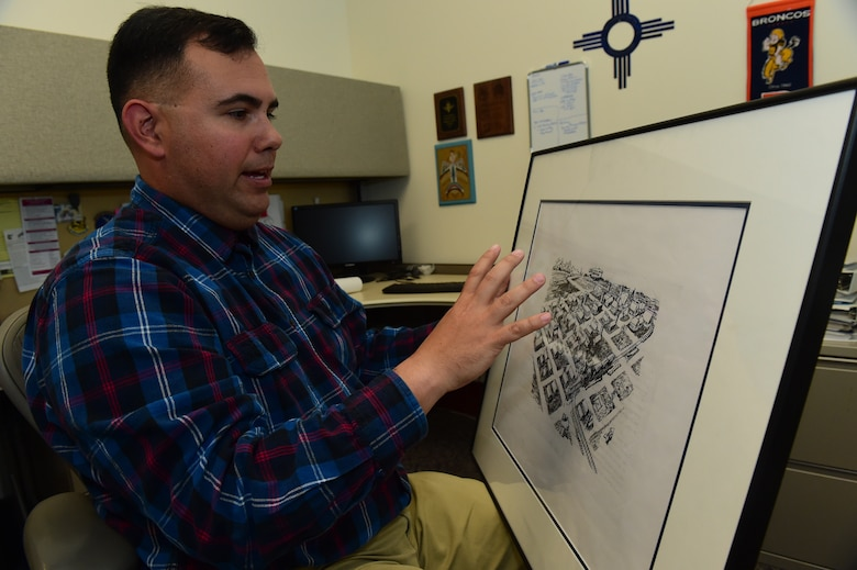 Christopher McCune, 460th Space Wing historian, explains a historical map Sept. 26, 2016, at the 460th Space Wing Headquarters building on Buckley AFB, Colo. As a historian, McCune must provide commanders with historical information to broaden their decision making ability that can affect today's mission. (U.S. Air Force photo by Airman 1st Class Gabrielle Spradling/Released)