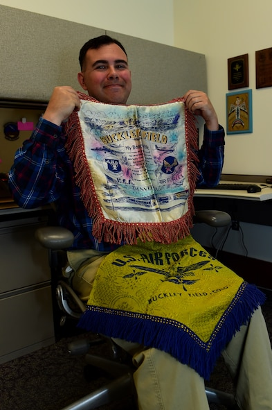 Christopher McCune, 460th Space Wing historian, displays a blanket and pillow cover from Buckley Air Force Base's past Sept. 26, 2016, at the 460th Space Wing Headquarters building on Buckley AFB, Colo. U.S. Air Force Historians, like McCune, are responsible for maintaining historic artifacts, such as newspapers. (U.S. Air Force photo by Airman 1st Class Gabrielle Spradling/Released)