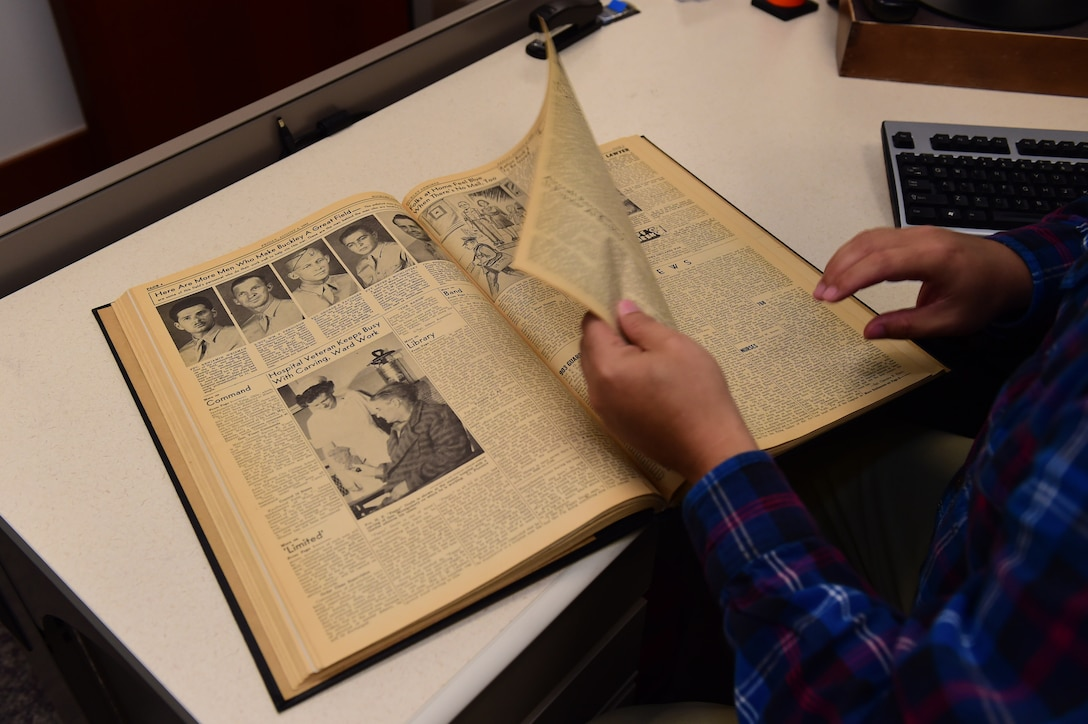 Christopher McCune, 460th Space Wing historian, turns a page in a book documenting the 1943 Buckley newspaper editions Sept. 26, 2016, at the 460th Space Wing Headquarters building on Buckley Air Force Base, Colo. A historian's core responsibility is documenting and sustaining the heritage of Air Force organizations. (U.S. Air Force photo by Airman 1st Class Gabrielle Spradling/Released)