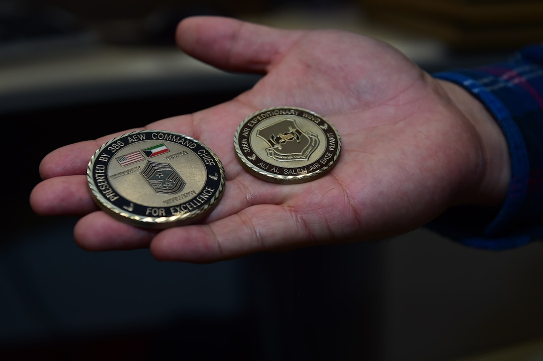 Christopher McCune, 460th Space Wing historian, displays two coins he received while on deployment Sept. 26, 2016, at the 460th Wing Headquarters building on Buckley Air Force Base, Colo. U.S Air Force historians serve as one of the few civilian positions within the federal government that receive deployment taskers. (U.S. Air Force photo by Airman 1st Class Gabrielle Spradling/Released)