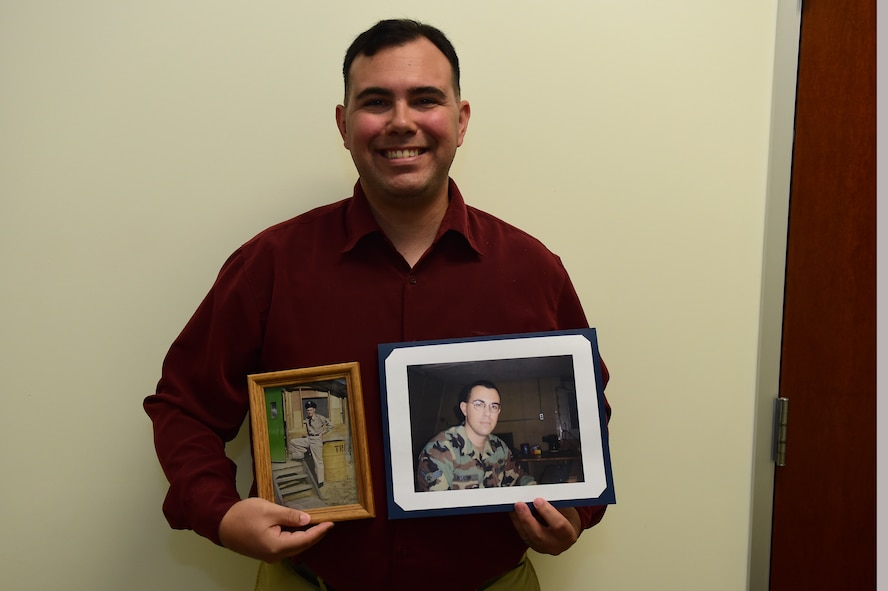 Christopher McCune, 460th Space Wing historian, displays photos of himself and his grandfather during their time in service Sept. 27, 2016, at the 460th Wing Headquarters building on Buckley Air Force Base, Colo. Most Air Force historians possess prior military experience, McCune included, which is helpful to obtaining a security clearance to perform their duties. (U.S. Air Force photo by Airman 1st Class Gabrielle Spradling/Released)