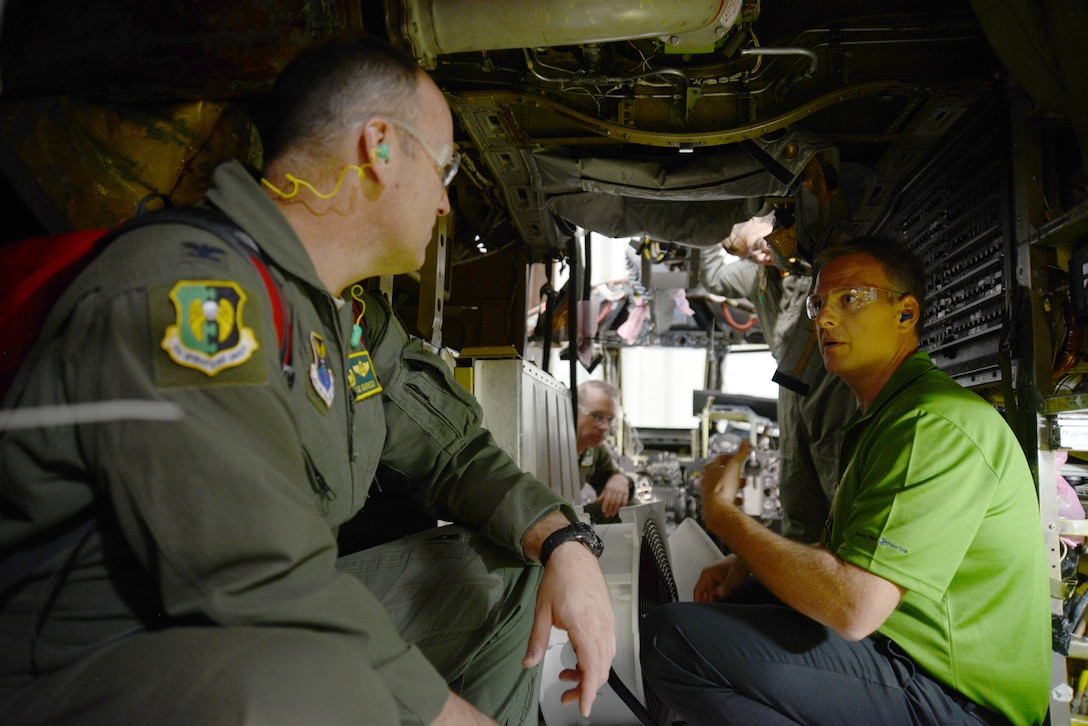 """Col. Doug Warnock, 5th Operations Group commander, a member of the B-52 crew from Minot Air Force Base, N.D., that came to take the """"Ghost Rider"""" home, gets a first-hand look at the installation of the Combat Network Communication Technology system from Mr. Heath Burnett, B-52H Avionics/Electrics Section Chief. Colonel Warnock was joined on the Sept. 27 tour of the B-52 programmed depot maintenance line by other crew members Lt. Col. Ryan McGough, Lt. Col. Jeremy Holmes, 1st Lt. Adam Carr and 1st Lt. Nathan Fisher. (Air Force photo by Kelly White)"""