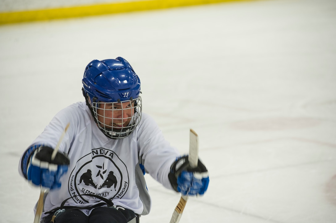 """Master Sgt. Richard Ortega, Fairchild Falcons varsity hockey team president, races toward a puck during the exhibition sled hockey match at the Frontier Ice Arena here in Coeur d'Alene, Idaho, Sept. 23, 2016. Instead of ice skates on their feet, sled hockey athletes are outfitted with sleds and short hockey sticks with metal """"teeth."""" The teeth allow for traction on the ice and propels the players in the direction of their choice. (U.S. Air Force photo/Tech. Sgt. Travis Edwards)"""