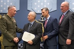 Marine Corps Gen. Joe Dunford, chairman of the Joint Chiefs of Staff, congratulates a representative for the Dryhootch Peer Support Program, one of the Newman's Own Award recipients, during a ceremony at the Pentagon, Sept. 29, 2016. DoD photo by Army Sgt. James K. McCann