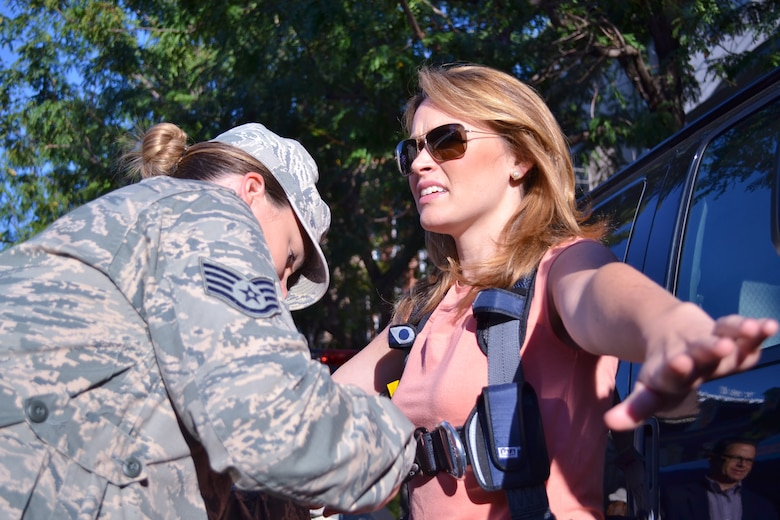 FOX News affiliate's FOX 29 Anchor and Reporter Karen Hepp is secured before being lifted in an Air National Guard bucket truck by Staff Sgt. Michele Hreso, 270th Engineering Installation Squadron member from Horsham Air Guard Station, Pa., during the FOX 29 Salutes the Military event Sept. 23, 2016 in center city Philadelphia. Pa. National Guard members joined members from all other services during the annual event held by the local FOX News affiliate. (U.S. Air National Guard photo by Tech. Sgt. Andria Allmond)