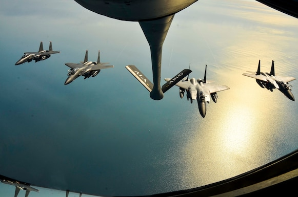 A four-ship of F-15E Strike Eagles, from the 494th Fighter Squadron, RAF Lakenheath, England fly in formation behind a KC-135R Stratotanker from the 117th Air Refueling Wing, Aug. 24, 2016, over the Atlantic Ocean. (U.S. Air National Guard photo by: Senior Airman Wesley Jones)