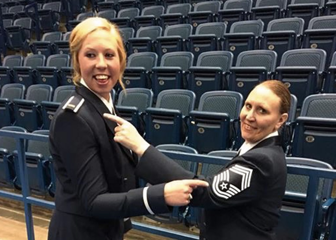 United States Air Force Academy graduate 2nd Lt. Taylor Parker and 120th Airlift Wing Chief Master Sgt. Teresa Parker point to each other's rank following the USAF Academy commissioning ceremony June 2, 2016. The daughter and mother received their rank on the same day. (Photo courtesy Parker family)