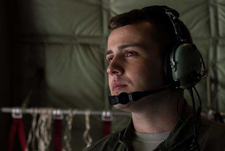 Senior Airman Anthony Oldham, 37th Airlift Squadron loadmaster, listens to communications from the cockpit while flying aboard a C-130J Hercules over the skies of Germany, Sept. 21, 2016. Oldham used some of the lessons his father, a retired Air Force Survival, Evasion, Resistance, and Escape instructor, taught him to save a civilian's life while on temporary assignment to Poland, Oct. 17, 2015. (U.S. Air Force photo by Senior Airman Nesha Humes)