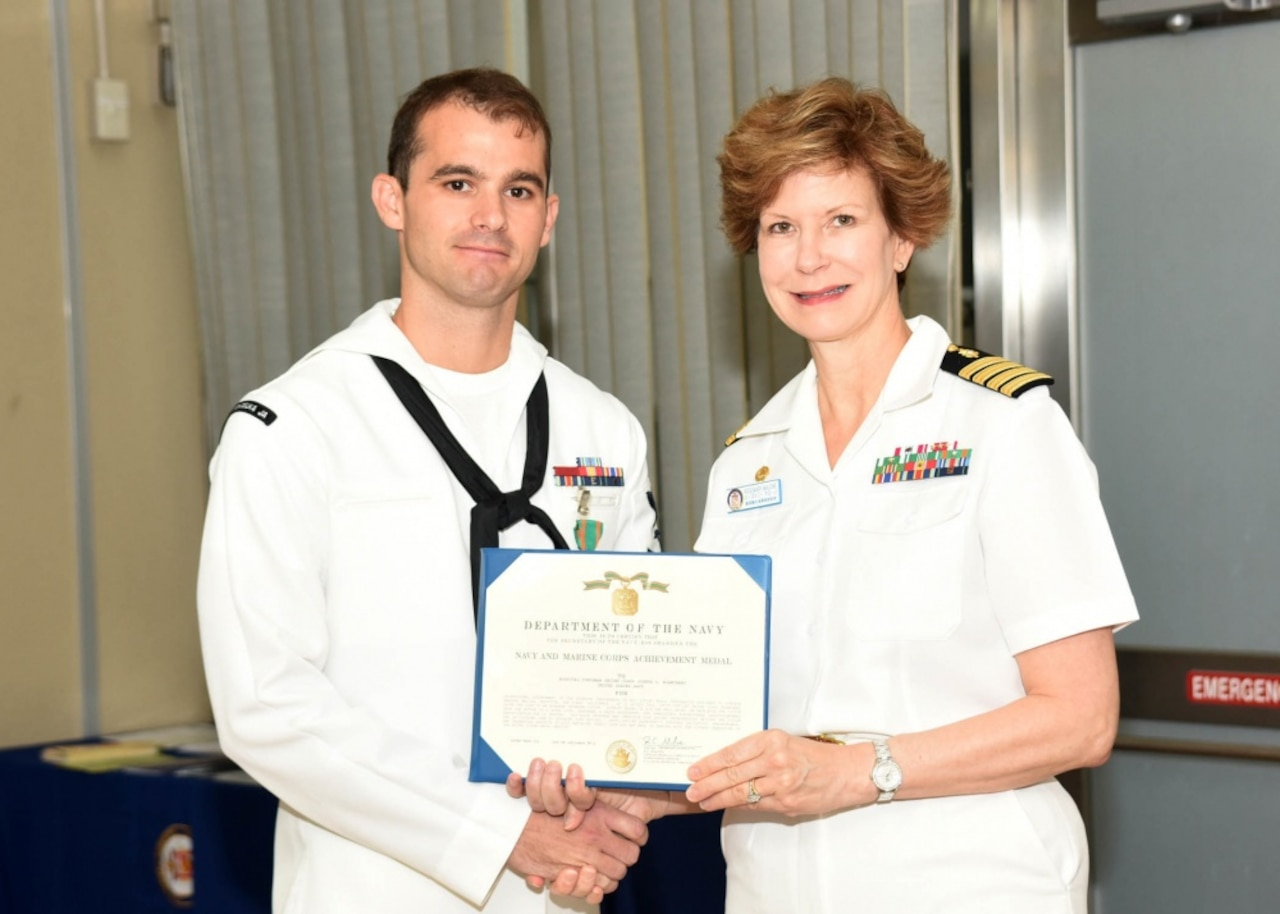 U.S. Naval Hospital Yokosuka's commanding officer, Navy Capt. Rosemary C. Malone, right, presents the Navy and Marine Corps Achievement Medal to Navy Petty Officer 2nd Class Joshua Blanchard, a hospital corpsman, during a ceremony at the Japan-based hospital, Sept. 13, 2016. Blanchard was honored for saving the life of a drowning mother on Aug. 16, 2016, during his temporary duty at the Surface Warfare Medical Institute in San Diego. Navy photo by Gregory Mitchell