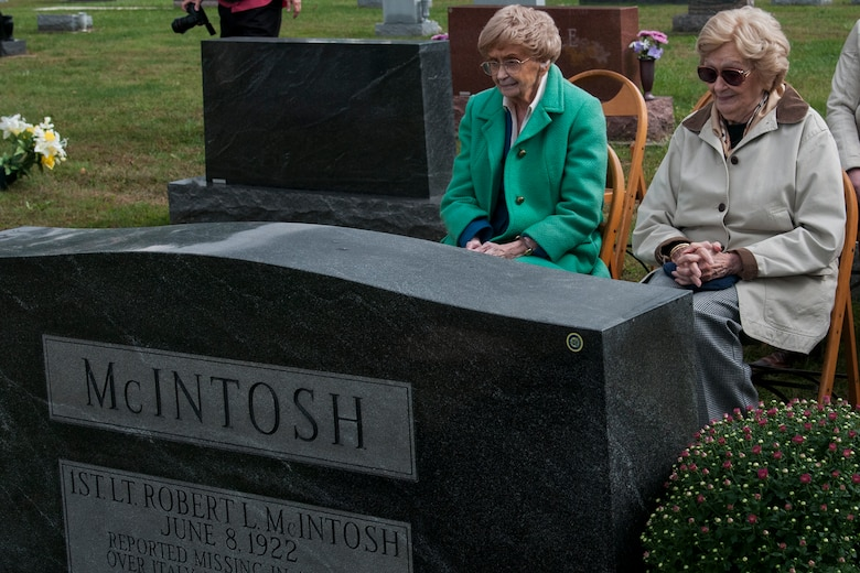 Patricia Talley and Jeannine Baker-McIntosh, sisters of Army Air Corps Lt. Robert McIntosh, 27th Fighter Squadron pilot, sit in front of their brother's tombstone before a flyover Sept. 29, 2016 in Tipton, Ind. McIntosh's aircraft crashed in 1942 and his remains were recently returned home. (U.S. Air Force photo/Staff Sgt. Dakota Bergl)