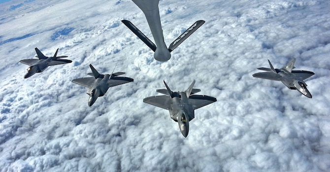 Four F-22 Raptors from the 27th Fighter Squadron out of Joint Base Langley-Eustis, Va., fly in formation below a 434th Air Refueling Wing KC-135R Stratotanker from Grissom Air Reserve Base, Ind., prior to a flyover in Tipton, Ind., Sept. 29, 2016.  The flyover was part of a memorial ceremony for Army Air Corps Lt. Robert McIntosh, who passed away after his aircraft crashed during World War II. (U.S. Air Force Photo/Col. Hiram Gates)
