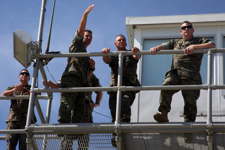 """Brig. Gen. Matthew Glavy stands on top of a control tower with Lt. Col. Matthew Simmons (left), Col. Paul Baker (center left) and Maj. Adam McArthur (right) from the outlying field working group during a visit aboard Marine Corps Auxiliary Landing Field Bogue, N.C., Sept. 28, 2016. Glavy visited the airfield to thank Marines for their hard work, to better understand the challenges they overcome on a daily basis and set eyes on supporting facilities to ensure they are maintained to high standards. """"Bogue represents the 2nd Marine Aircraft Wing's ability to conduct expeditionary operations,"""" said Glavy. """"They provide aviation ground support, air traffic control and operational support to the aircraft that rely on them. It is a unique place where 2nd MAW can get critical expeditionary training that we cannot receive anywhere else."""" Glavy is the commanding general for 2nd MAW, Simmons is the assistant chief of staff in the 2nd MAW G6, Baker is the officer in charge of the aviation ground support department and McArthur is the aviation ranges project lead in 2nd MAW G3. (U.S. Marine Corps photo by Lance Cpl. Mackenzie Gibson/Released)"""