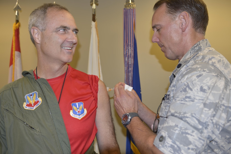 """Lt. Gen. Scott Williams, Commander, 1st  Air Force (Air Forces Northern) and Commander, Continental U.S. North American Aerospace Defense Command Region, asks Lt. Col. Greg Martin, 1st Air Force surgeon's office, """"Did you already give me the shot?"""" after the painless flu shot. Williams was first in line for the flu shot season Sept. 30.  The 1st AF surgeon's office is aiming to administer flu shots to approximately 600 command personnel. Martin has overseen the flu shot program at 1st AF for the past four years.  (U.S. Air Force photo by Tom Saunders)"""
