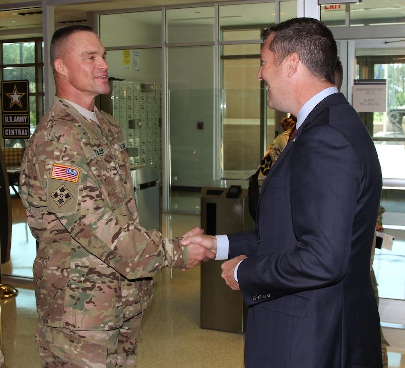 The Honorable Patrick Murphy (right), undersecretary of the Army, gives Maj. James Taylor, an exercise planner assigned to the information operations directorate of U.S. Army Central, a coin for excellence for his entering and winning of an Army body building competition earlier this year.