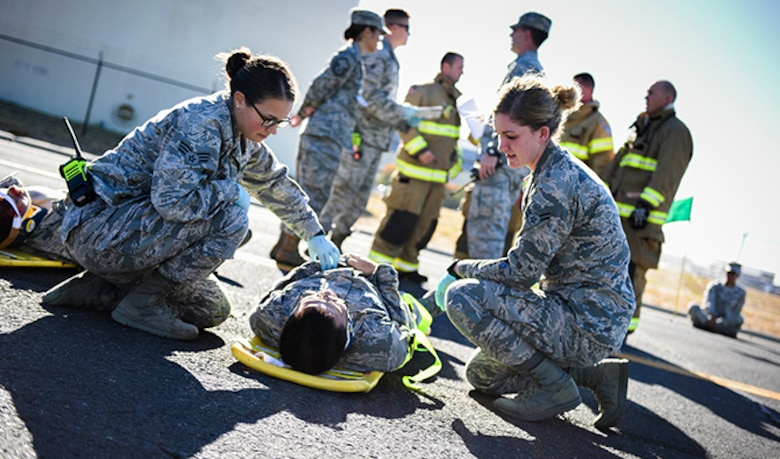 Senior Airman Julie Fink, 92nd Medical Operations Squadron aerospace medical technician, and Airman 1st Class Shawn McMahan, 92nd Medical Operations Squadron emergency medical technician, provides medical care to a simulated victim of a vehicle incident during an Emergency Management Exercise Sept. 27, 2016, at Fairchild Air Force Base, Wash. The base participates in different types of scenarios and situations, to be prepared when an incident occurs. (U.S. Air Force photo/Airman 1st Class Sean Campbell)