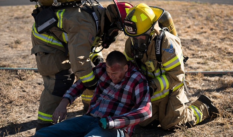 Team Fairchild firefighters help up a simulated wounded civilian during an Emergency Management Exercise Sept. 29, 2016, at Fairchild Air Force Base, Wash. Securing the scene of an emergency, assisting and safely evacuating causalities is the role every first responder undergoes rigorous training for. (U.S. Air Force photo/Airman 1st Class Ryan Lackey)