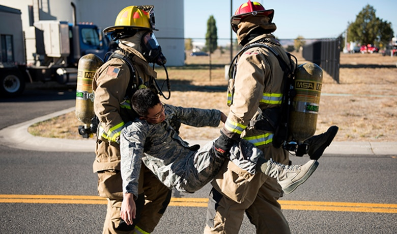 A pair of Team Fairchild firefighters carry an unconscious Airman away from the scene of an accident during an Emergency Management Exercise Sept. 29, 2016, at Fairchild Air Force Base, Wash. Multiple casualties allow Airmen to gain experience during these exercises. (U.S. Air Force photo/Airman 1st Class Ryan Lackey)