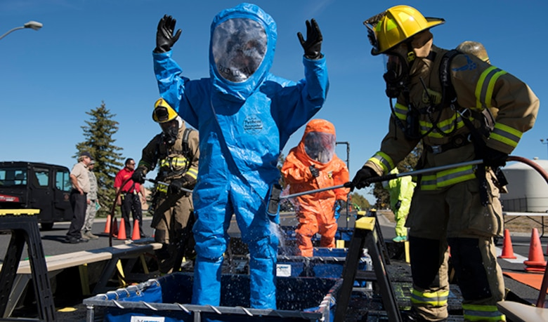 Firefighters from the 92nd Civil Engineer Squadron assist in decontaminating a hazardous materials team's protective suits after responding to a chemical leak during an Emergency Management Exercise Sept. 29, 2016, at Fairchild Air Force Base, Wash. Exercises allow Airmen to practice vital skills in various formats to keep emergency response abilities sharp in the event of an actual crisis. (U.S. Air Force photo/Airman 1st Class Ryan Lackey)