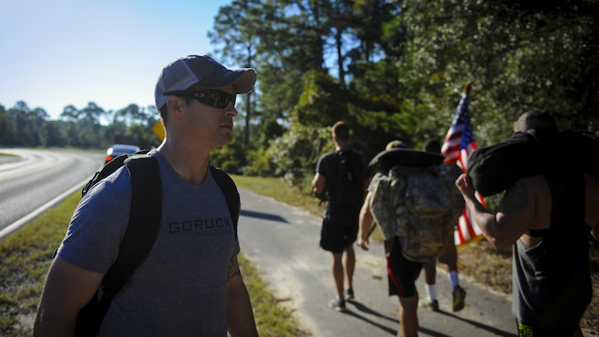 Kevin Randolph, the cadre of the Air Force Special Operation Command Team Cohesion Challenge, guides the formation as they march to the next exercise at Hurlburt Field, Fla., Sept. 29, 2016. Randolph travels to various locations leading team cohesion challenges to teach people to work as a team through difficult circumstances. (U.S. Air Force photo by Airman Dennis Spain)