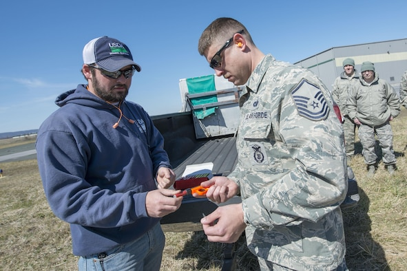 Chad Neil, a wildlife specialist for U.S. Department of Agriculture Animal Plant Health Inspection Service Wildlife Service - West Virginia, assists Master Sgt. Patrick Judy, 167th Airlift Wing Security Forces, with a pyrotechnics pistol as part of a wildlife management course taught at the wing, March 23. Pyrotechnics are one of the tactics used to scare away birds from the airfield for the safety of the aircraft and the animals. (U.S. Air National Guard photo by Senior Master Sgt. Emily Beightol-Deyerle)