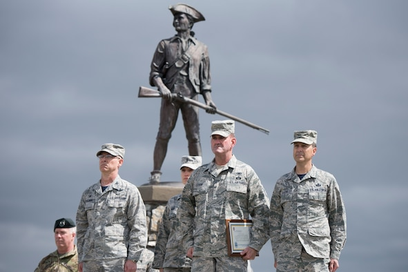 Col. Shaun J. Perkowski, 167th Airlift Wing commander, Chief Master Sgt. David Stevens, incoming wing command chief, and Chief Master Sgt. Ronald R. Glazer, Sr., outgoing command chief, stand at attention during the change of responsibility ceremony held in front of the minuteman statue at the 167th Airlift Wing, April 1. (U.S. Air National Guard photo by Senior Master Sgt. Emily Beightol-Deyerle)