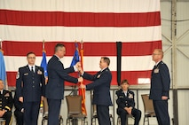 SIOUX FALLS, S.D. - Col. Nate Alholinna, 114th Fighter Wing commander, hands off the flag of the 114th Maintenance Group to Lt. Col. Kevin Curley during a change of command ceremony at Joe Foss field April 1st.  Curley assumed command of the 480 airmen in the maintenance group and will oversee 22 assigned shops and 30 Air Force Specialty Codes.  (U.S. Air National Guard photo by Master Sgt. Christopher Stewart/Released)