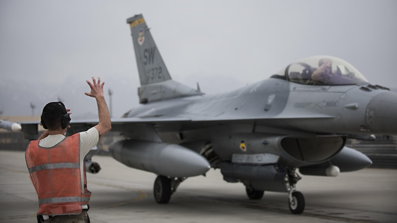 Staff Sgt. Ryan Best, 455th Expeditionary Aircraft Maintenance Squadron weapons load crew member, and Lt. Col. Craig Andrle, 79th Expeditionary Fighter Squadron commander, show tiger claws, representing the fighter squadron's mascot, after a combat sortie March 20, 2017 at Bagram Airfield, Afghanistan. Andrle reached a milestone 1,000 combat hours while supporting the wing's counterterrorism mission in Afghanistan. (U.S. Air Force photo by Staff Sgt. Katherine Spessa)