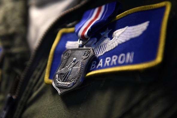 U.S. Air Force Maj. Nathan Barron, 156th Airlift Wing, shows his family the North Carolina National Guard Soldier and Airman Medal for heroism after a presentation ceremony held at the North Carolina Air National Guard Base, Charlotte Douglas International Airport, April 1, 2017. Barron was awarded the medal for his decisive and courageous actions as civilian pilot on a PSA Airlines flight where he tackling and maneuvering an unruly passenger to the ground after he assaulted a flight attendant. Barron continued to subdue the passenger until law enforcement arrived which saved the lives of the crew as well as others aboard the plane. The medal was recently created to honor Soldiers and Airmen for heroic actions performed while out of the military uniform.