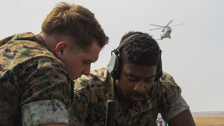 U.S. Marine Corps Lance Cpls. Kevin McKee, left, and Byron Armstrong, right, communications technicians with Marine Air Control Squadron 4, talk to Japan Maritime Self-Defense Force helicopter pilots during a cross-training exercise at Marine Corps Air Station Iwakuni, Japan, March 30, 2017. The Marines took part in a simulated forward arming and refueling points operation, where they communicated with JMSDF helicopter pilots to perform austere landings on a heliport that acted as an expeditionary runway.