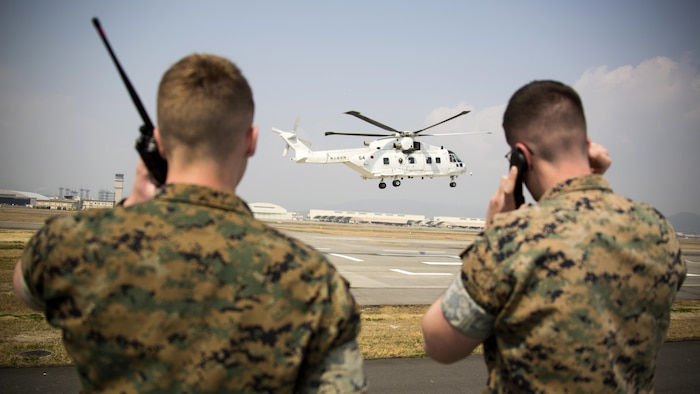 U.S. Marine Corps Lance Cpl. Daniel McGinness, left, and U.S. Marine Corps Cpl. Stephen Wellman, right, air traffic controllers with Headquarters and Headquarters Squadron, guide Japan Maritime Self-Defense Force helicopter pilots onto a designated landing site during a cross-training exercise at Marine Corps Air Station Iwakuni, Japan, March 30, 2017. The Marines took part in a simulated forward arming and refueling points operation, where they communicated with JMSDF helicopter pilots to perform austere landings on a heliport that acted as an expeditionary runway.
