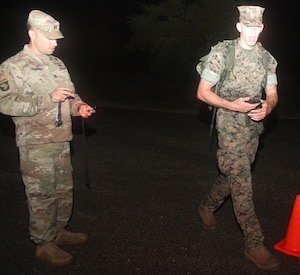 Seaman Adam Wild (right) shouts out his battle roster number at the half-way point of the 12-kilometer foot march on at Joint Base San Antonio-Camp Bullis April 2. Competitors carried a 33-pound rucksack during the final event of the three-day German Armed Forces Proficiency Badge testing.