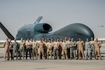 Members of the 380th Expeditionary Aircraft Maintenance Squadron and the 99th Expeditionary Reconnaissance Squadron pose for a group photo after successfully completing 1000 consecutive sorties without a maintenance cancel in support of Combined Joint Task Force-Operation Inherent Resolve at an undisclosed location, April 1, 2017. These remotely piloted aircraft have provided a critical communication bridge between multi-national Coalition assets working to defeat ISIS in the area of responsibility. (U.S. Air Force/Senior Airman Tyler Woodward)