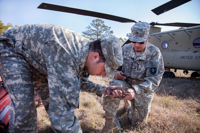 Georgia Army National Guard Sgt. Mike Griffith, right, and Sgt. Ryan Bragg prepare a bucket firefighting system to be attached to a CH-47 Chinook helicopter during aerial firefighting exercise Operation Vigilant Guard in Ellabell, Ga., March 29, 2017. Griffith and Bragg are assigned to the Georgia Army National Guard's Detachment 1, Company B, 1st Battalion, 169th Aviation Regiment. Army photo by Spc. Jesse Coggins