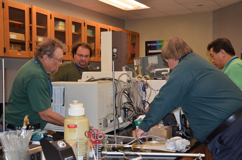 George Kenney, left, and Scott Herber, second from left, help Dr. Dan Mackney and Dr. Zhengrong Lee place a mass spectrometer on a lab table at Eastern Florida State College March 17, 2017.  Mackney and his co-workers from the Air Force Technical Applications Center, Patrick AFB, Fla., assisted Kenney, Herber and Lee, all science professors at EFSC, procure lab analysis equipment from an anonymous Central Florida donor. (U.S. Air Force photo by Susan A. Romano)