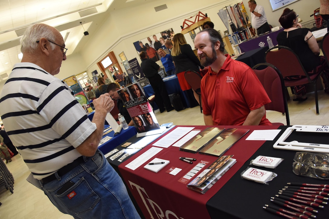 Rob Morrison, Troy University military and family representative and recruiter, provides information to retired Master Sgt. Dennis Roach during the Spring Education Information Fair at the base exchange, March 29, 2017, on Keesler Air Force Base, Miss. The Keesler Education Services' staff hosted more than 25 community colleges and universities at the event. (U.S. Air Force photo by Kemberly Groue)