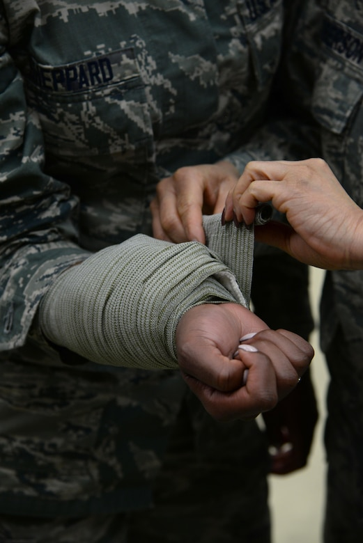 Maj. Asia Roberson, 86th Medical Group infection and disease manager, applies a pressure dressing bandage to Senior Airman Shaquelle Sheppard, 86th Medical Support Squadron patient movement technician, during an 86th Medical Group training day on Ramstein Air Base, Germany, March 22, 2017. The pressure dressing bandage is used to stop bleeding in patients. (U.S. Air Force photo by Airman 1st Class D. Blake Browning)