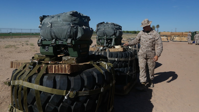 U.S Marine Pfc. Brad A. Clark inspects the rigged aerial delivery systems of Joint Precision Airdrops during a Weapons and Training Instructor Course March 30, 2017, at Marine Corps Air Station Yuma, Ariz. Clark is an airborne delivery specialist with 2nd Transportation Support Battalion, 2nd Marine Logistics Group. The JPADS uses a GPS system and a modular autonomous guidance unit to get to their targeted drop zones.