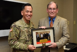 Brig. Gen. Mark Toy, Great Lakes and Ohio River Division commander in Cincinnati, Ohio, congratulates Mike Wilson, U.S. Army Corps of Engineers Nashville District deputy for Programs and Project Management, on his upcoming retirement and presents him a photo of him and all of his counterparts while visiting the Nashville District headquarters in Nashville, Tenn., March 16, 2017.